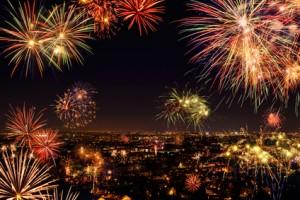 Lebhaftes buntes Feuerwerk über einer Stadt, gesehen von oben